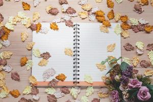 Spiral notebook with maple leaves on wood background photo