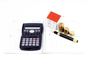 Mortgage loan planning with fountain pen and calculator and coins and paper house on calendar book pages for loans concept photo