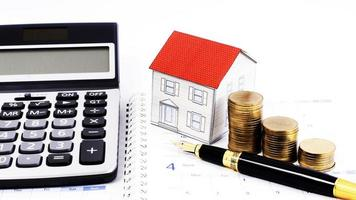 Mortgage loans concept with Fountain pen and money coins stack and paper house and calculator on calendar book pages photo