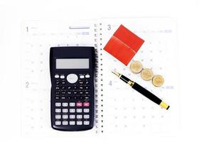 Mortgage loan planning concept with fountain pen and calculator and coins and paper house on calendar book pages photo