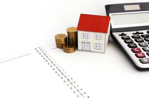 Home loans concept with paper house and coins stack and calculate on book pages photo