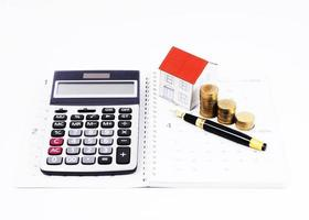 Home loans concept with Calculator and Fountain pen and paper house and money coins stack on calendar book pages photo