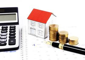 Close up for Fountain pen and money coins stack and paper house and calculator on calendar book pages photo