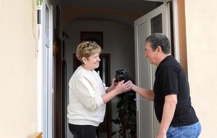 Women greeting men at doorway photo