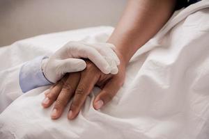 Mano del doctor tranquilizando a su paciente femenino concepto de apoyo y atención de cerca foto