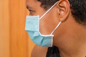 Black man with blue protective mask against coronavirus in rio de janeiro photo