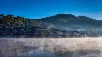 Rakthai village with mist from lake in morning at Mae Hong Son, Thailand photo