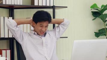 l'uomo asiatico è seduto in un ufficio moderno che ha dolore a causa delle lunghe ore di lavoro video