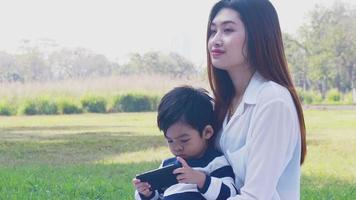 Asian mother and son happily play with toys in the park video