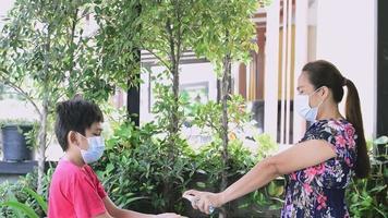 mãe estava borrifando álcool para limpar as mãos do filho, enquanto usava uma máscara de pano para prevenir infecção secreta video