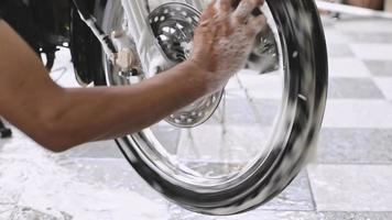 Close up of a man hand washing a motorbike front wheels with sponges and bubbles video