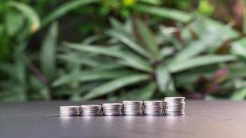 Time lapse video of  stacked rows of coins on a table with green leaves in the garden background