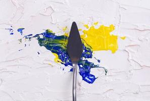 A painting palette knife isolated on a white painted background painting a blue and yellow with copy space photo