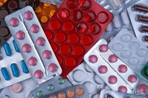 Montón de píldoras médicas en blanco, azul y otros colores. foto