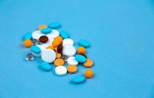 Multi colored pills on a blue background close-up photo