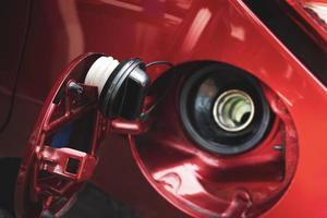 Tapón del depósito de combustible colgando de la puerta del depósito de combustible del coche rojo foto