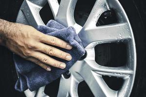 la mano humana está limpiando la rueda de aleación del automóvil con un paño de microfibra foto