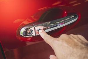 Mano humana presionando el botón de entrada sin llave en la manija de la puerta del automóvil del automóvil rojo foto