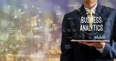 Businessman holding a tablet with the word business analytics photo