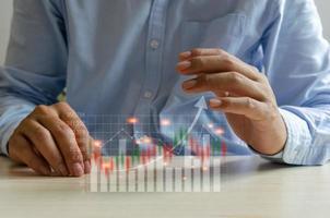 gráfico financiero empresarial frente a las manos de un hombre foto