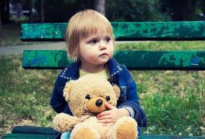 niño pequeño sentado en el banco en el parque foto