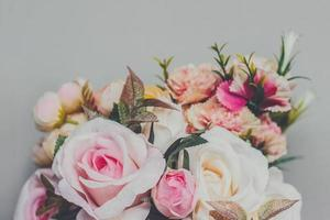 Bouquet of artificial pastel color flowers on gray background top view with copy space photo