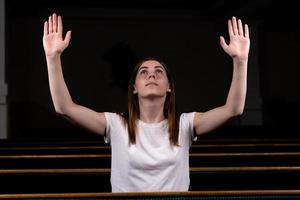 A Christian girl in white shirt is praying with humble heart in the church photo