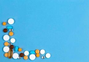 Pastillas de colores establecidos como borde sobre fondo azul con espacio para copiar texto foto