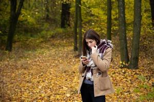 Cute girl in a brown jacket in the autumn forest photo