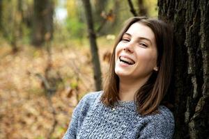 Young beautiful girl with braces on her teeth in a gray sweater sits in the autumn forest photo
