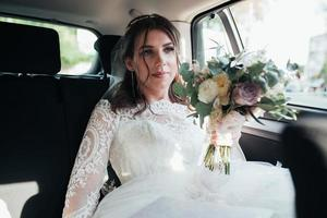 Wedding photo of the bride who is sitting in the car with a bouquet of flowers