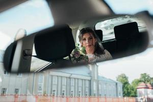 The reflection of the bride in the rearview mirror of the car photo