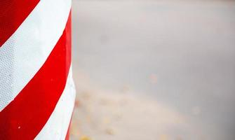 Red and white striped concrete road barrier close-up with copy space for text photo