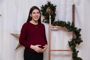 Hermosa niña embarazada sonriente de pie en el fondo de la decoración navideña foto