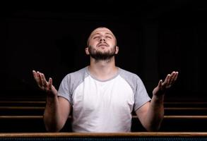 A Christian man in white shirt is sitting with his hands up and praying with humble heart in the church photo