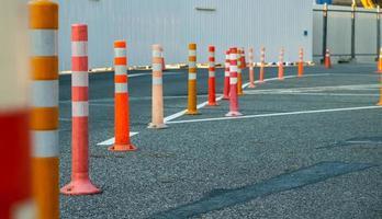 Poste de tráfico naranja en la carretera asfaltada en el estacionamiento foto