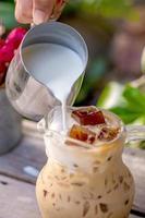 vertiendo leche en un vaso con café con leche y helado foto