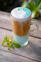 Menta de café helado en vaso con hojas de menta sobre fondo de mesa de madera foto