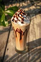 Coffee frappe with whipped cream on old wooden table in the morning sun photo