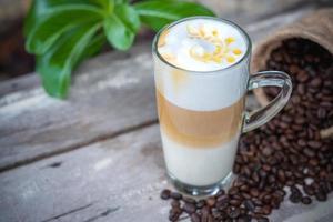 Café caramelo caliente en vaso con granos de café. foto