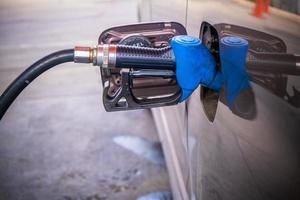 Holding blue fuel nozzle to refuel gasoline for car photo