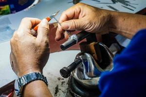 Close up of a goldsmith hand making silver ring photo