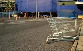 Carro de compras con cono de tráfico en el estacionamiento de la tienda fondo azul foto