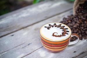 Café capuchino caliente en la mesa de madera antigua con granos de café tostados foto