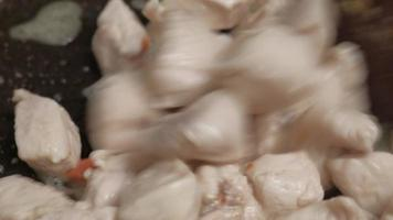 Roasting chicken meat in a brown pan, close-up video