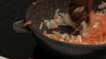Frying onions and carrots in a brown pan, close-up video