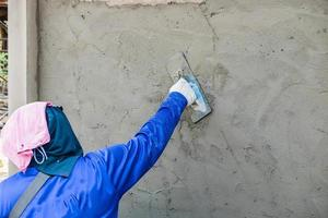 The plasterer is applying cement to the house wall photo
