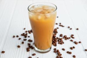 Café helado en un vaso sobre un fondo de madera blanca foto
