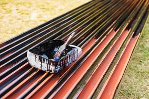 pincel sobre cubo de pintura para pintar acero, cinta para proteger contra la oxidación. foto