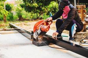 Ingeniero de corte de acero con cortador de hierro eléctrico foto